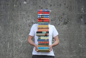 Mann mit Bücherstapel vor Gesicht